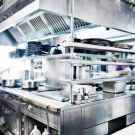 Man Stirring Pot in Stainless Steel Restaurant Kitchen
