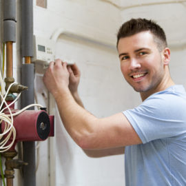 A repairman fixes a heating system while he smiles at the camera.