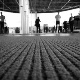 Perspective of doormat with background is blur of people. (selective focus, back and white image)