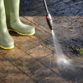 Photo showing a boy who is using a powerwasher / pressure-washer hose to wash a dirty block-paved drive, cleaning up the bricks with a strong jet of water.