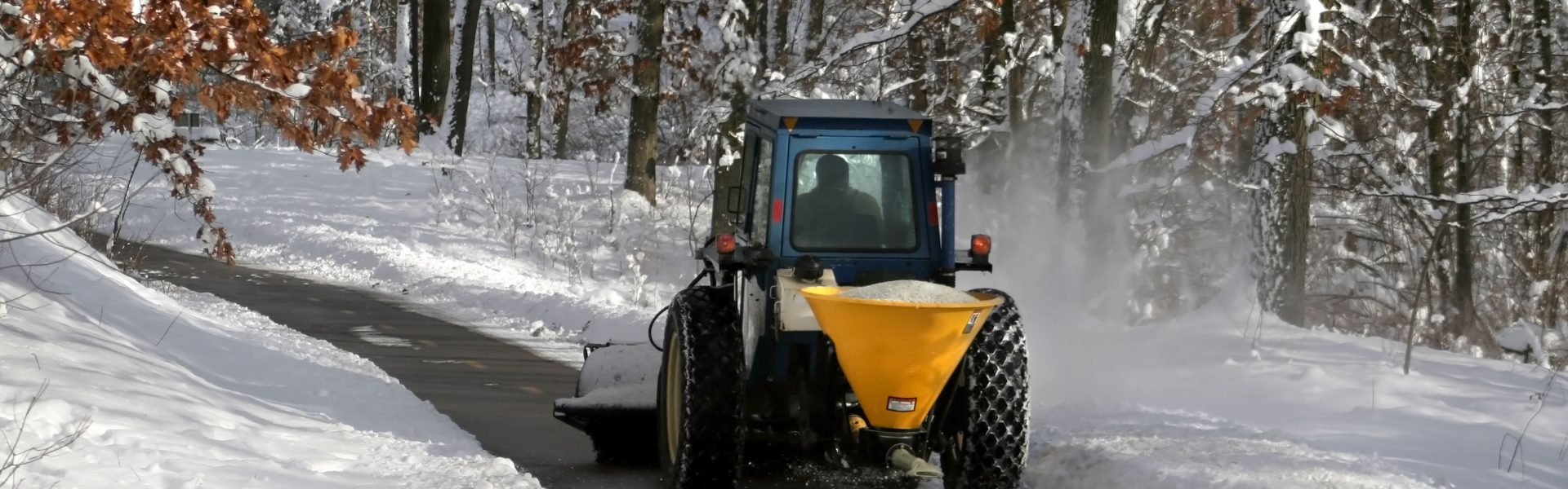 snow plowing machine cleaning the bike trail during winter time